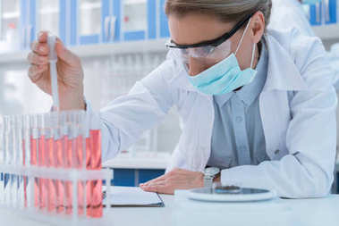 Professional scientist in sterile mask and protective glasses, making experiment with samples in chemical lab stock vector