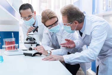 Professional scientists in white coats and sterile masks, doing microscope analysis and discussing work in laboratory stock vector