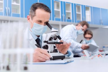 Scientist in lab coat and sterile mask doing microscope analysis while his colleagues are sitting behind stock vector