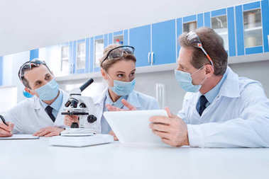Doctors in lab coats and sterile masks, doing microscope sample analysis and working with digital tablet stock vector