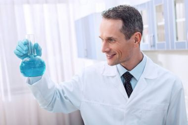 Smiling scientist in lab coat holding a flask with blue liquid stock vector