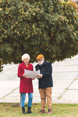 senior couple with map in park