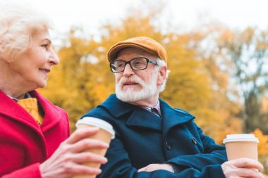 senior couple drinking coffee in park
