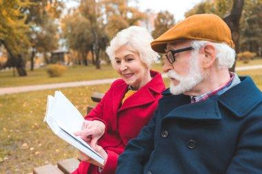 senior couple reading book in park