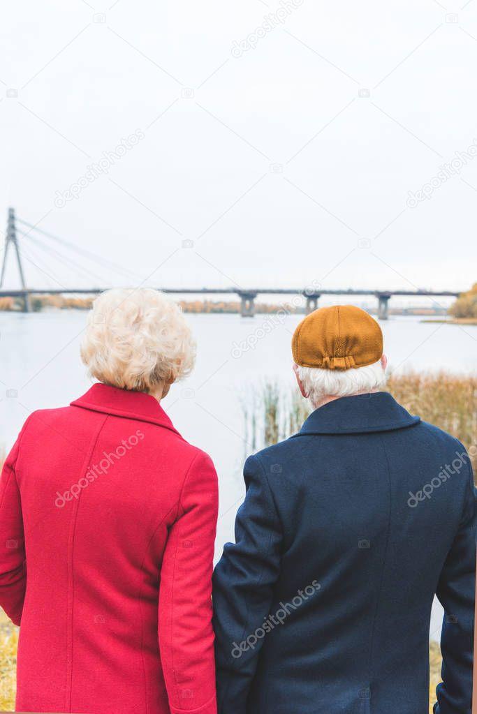 senior couple looking at autumn lake