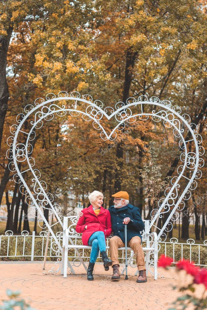 senior couple on heart shaped bench
