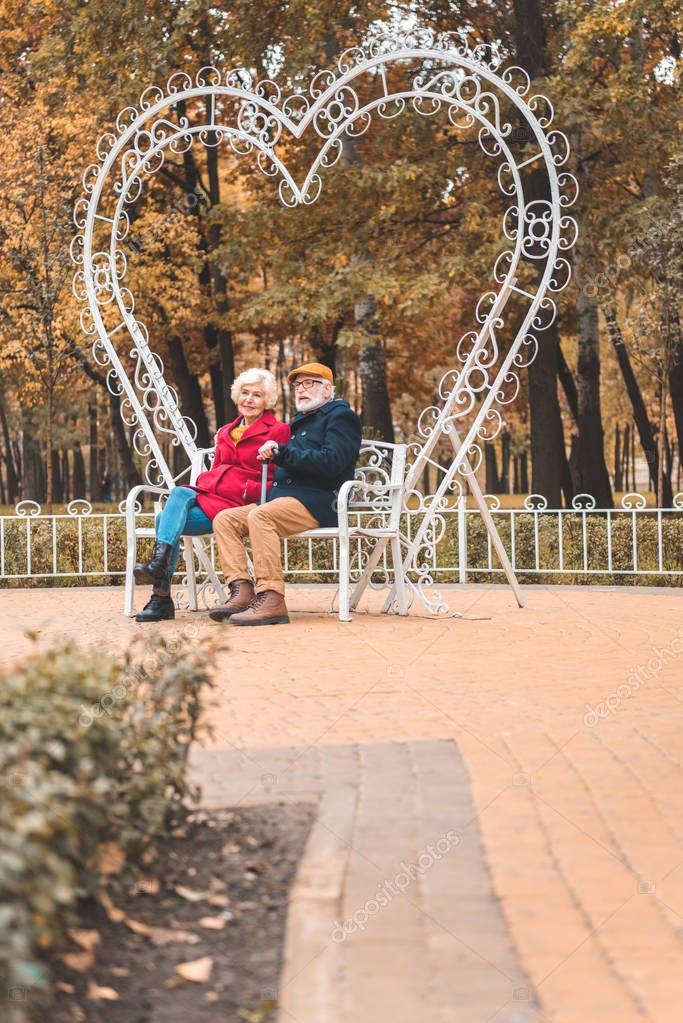 couple sitting on heart shaped bench
