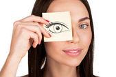 žena pokrývající oko s nálepkou