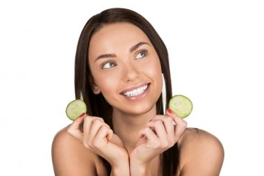 woman with slices of cucumber for skincare mask
