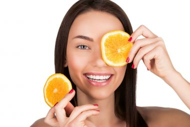 Attractive young woman with sliced orange for mask isolated on white stock vector