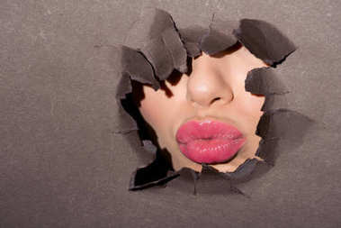 pink lips of woman in paper hole