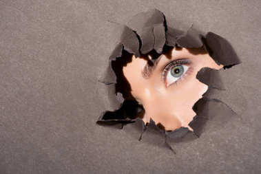 woman peeking out of hole in paper