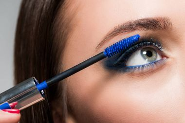 Cropped shot of young woman doing eyelashes makeup with blue brush stock vector