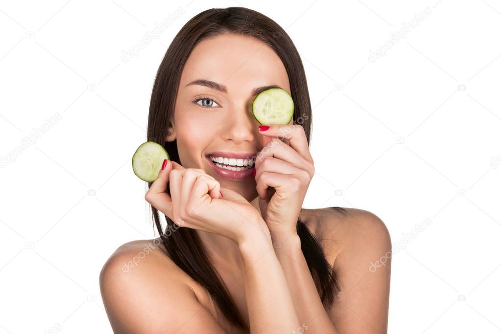 woman with sliced cucumber for skincare mask