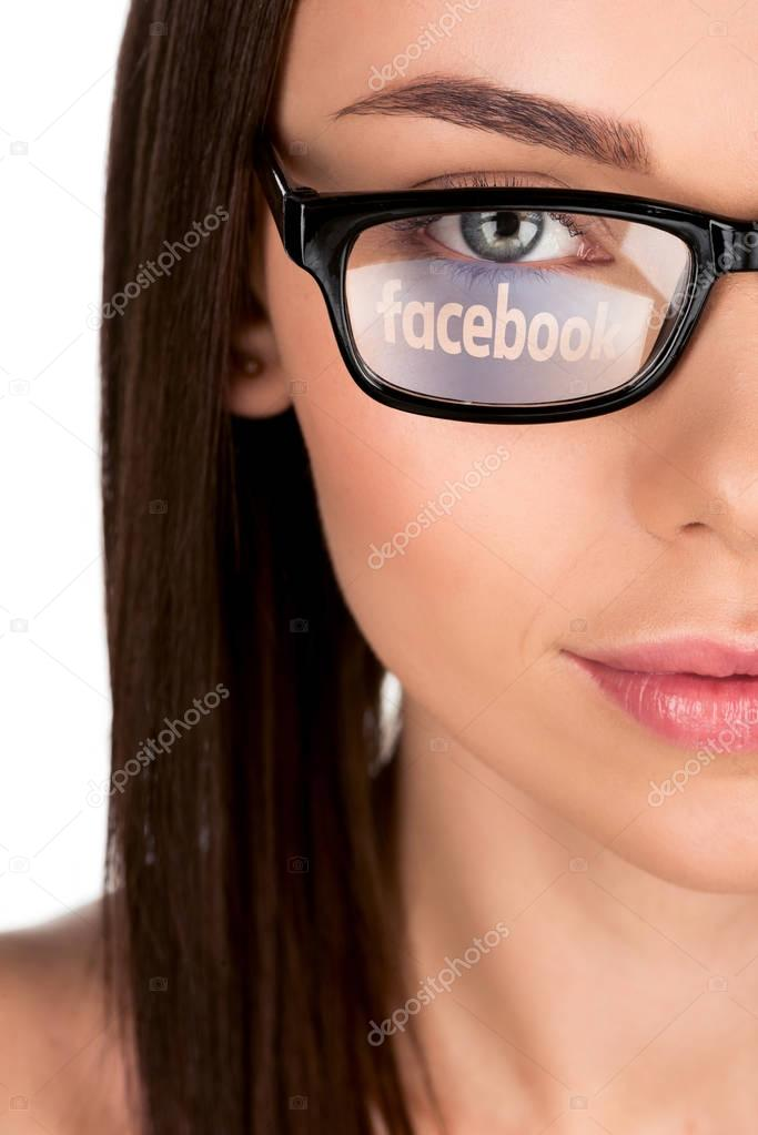woman with facebook logo reflection in eyeglasses