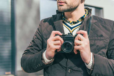 Cropped shot of young man holding camera on street stock vector