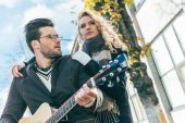couple in autumn outfit with guitar