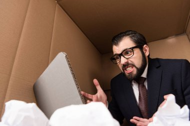 aggressive businessman with cardboard laptop