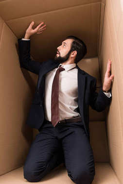 Businessman with claustrophobia kneeling in cardboard box stock vector