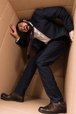 stressed businessman in cardboard box