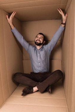 Cheerful man sitting in cardboard box, introvert concept stock vector