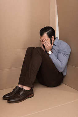 Depressed man crying and sitting in cardboard box stock vector