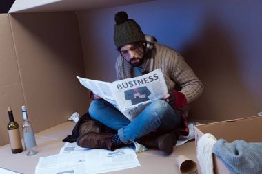 homeless with business newspaper