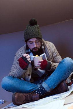 homeless man eating tinned food