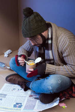 homeless man eating canned food