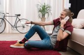 Fényképek beszélő smartphone otthon tévénézés közben jóképű férfi