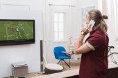 Fényképek ember beszél a smartphone, miközben nézi a labdarúgó-mérkőzés otthon