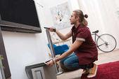 pohledný muž s dálkovým ovládáním a televize doma