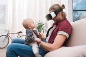 Fotografia Padre sorridente che si siede con la sua piccola figlia e utilizzando le cuffie da realtà virtuale
