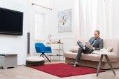 Fotografia uomo d affari using digital tablet stando seduti sul divano di casa