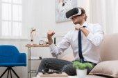 Fotografie Geschäftsmann, kämpfen und mit virtuellen Realität Kopfhörer beim Sitzen auf dem Sofa zu Hause