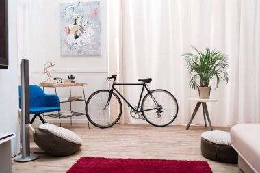 Bicycle standing in a living room near the window