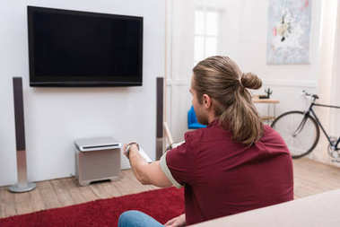 back view of man with remote watching tv at home