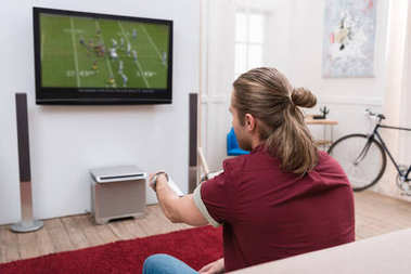 back view of man with remote control watching football match at home