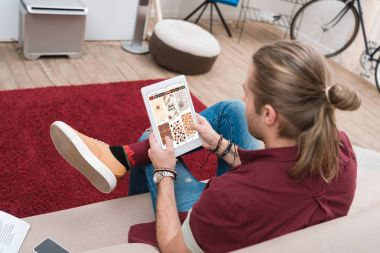 man sitting on sofa while using digital tablet with pinterest appliance