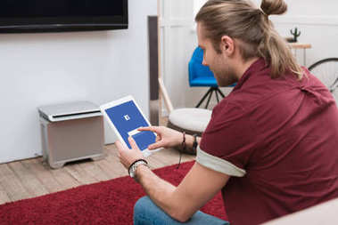 man sitting on sofa while using digital tablet with facebook appliance