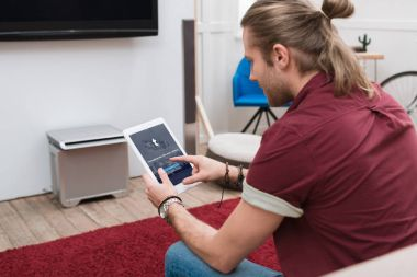 man sitting on sofa while using digital tablet with tumblr appliance