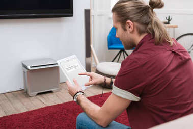 man sitting on sofa while using digital tablet with website