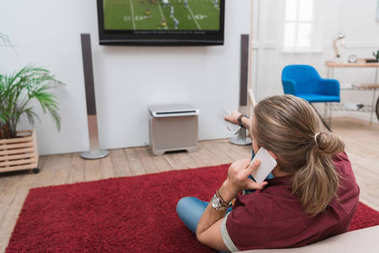 back view of man talking on smartphone while watching football match at home