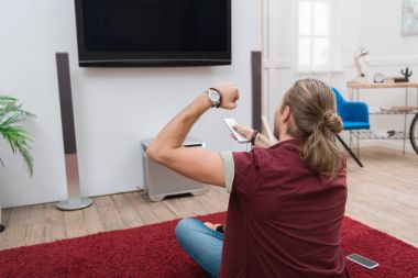 cheerful man with remote control gesturing and watching tv at home