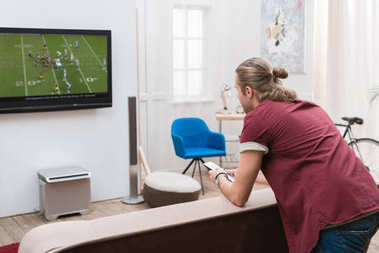 back view of man watching football match at home