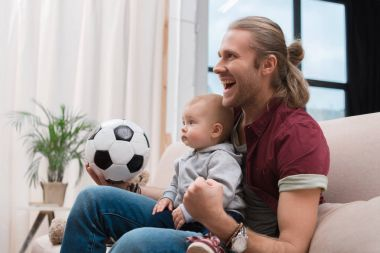 excited father with baby boy watching football match at home