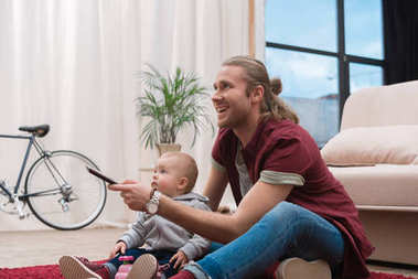 happy father watching TV with his little son at home
