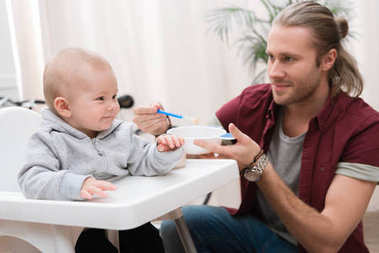father feeding his cheerful son with baby food at home