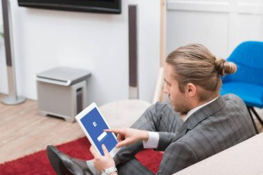 businessman using digital tablet with facebook website at home