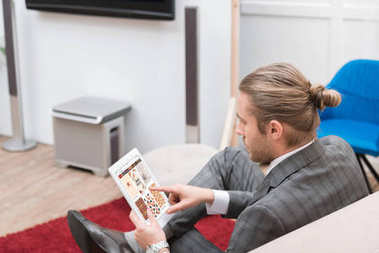 businessman using digital tablet with pinterest website at home